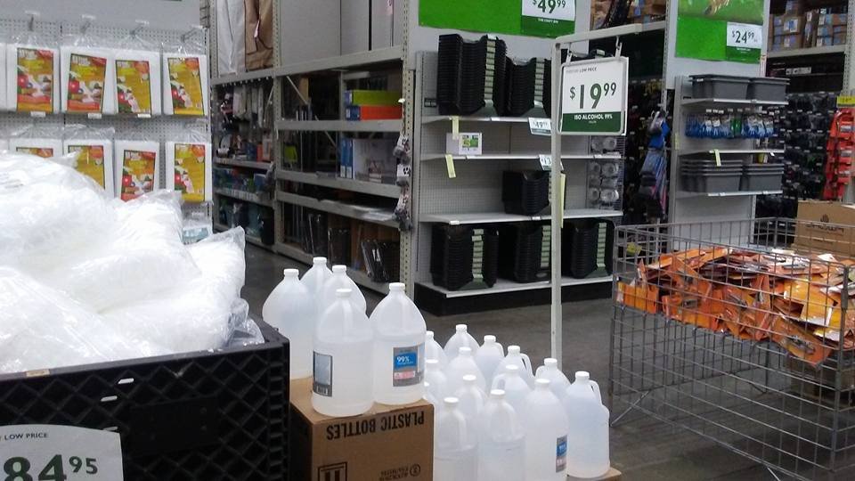 Gallons of rubbing alcohol, scissors, and gloves  make up the center displays at the local Friedman's. Trim bins are visible in the background.
